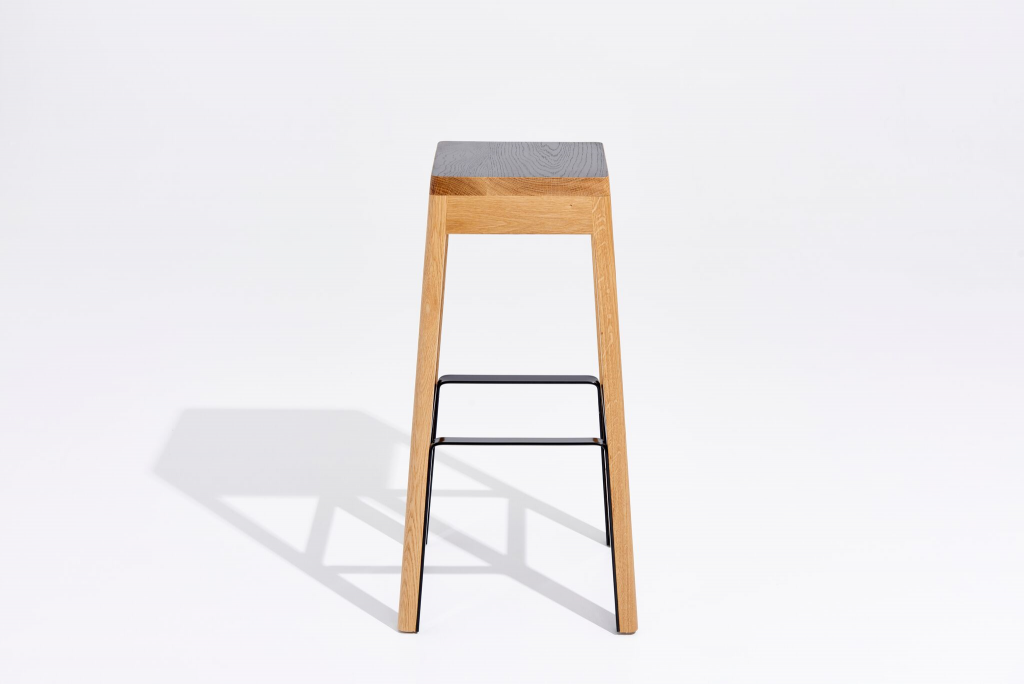 The aesthetic of the stool is created through black and natural tones