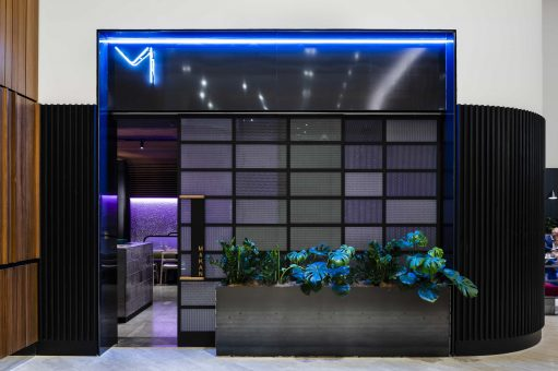 Intentionally Creating Separation Through The Entry Door, The Space Is Tonally Dark And Moody, With Continuous Illuminated Coloured Lighting Throughout