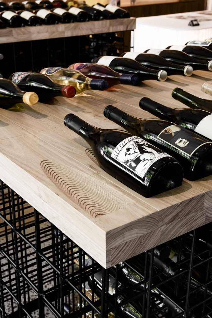 Freestanding Open Wire Display Frames Allow A Dynamic Storage Pattern Under Individually Routed Timber Blocks That House Each Wine Bottle.